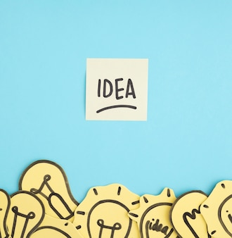 Idea text on sticky note over the different yellow light bulbs on blue background