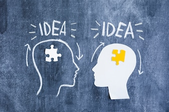 Idea text over the brain with white and yellow jigsaw puzzle on blackboard