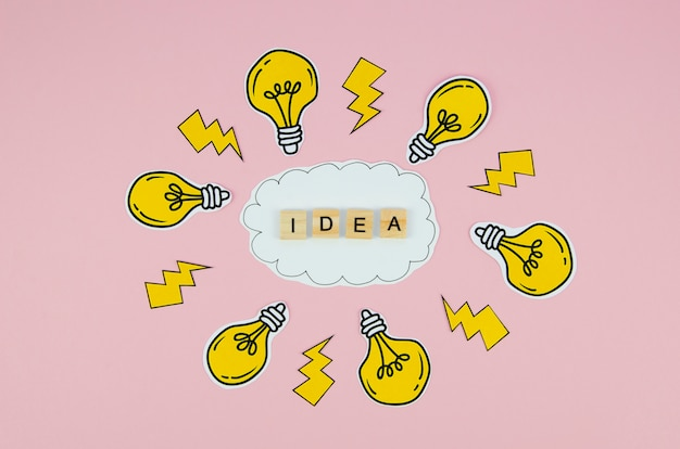 Idea text in scrabbles letter and light bulbs on pink background