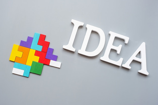 Idea text with colorful wood puzzle pieces on gray . logical thinking, business logic, conundrum, inspiration, solutions, rational, mission, success, goals and strategy concepts