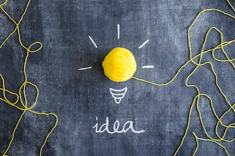 Idea text with yellow ball of wool as light bulb on chalkboard