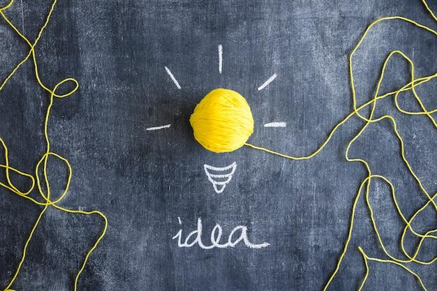 칠판에 전구로 양모의 노란 공을 가진 아이디어 텍스트