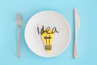 Idea text with yellow light bulb over the white plate with fork and butter knife against blue background