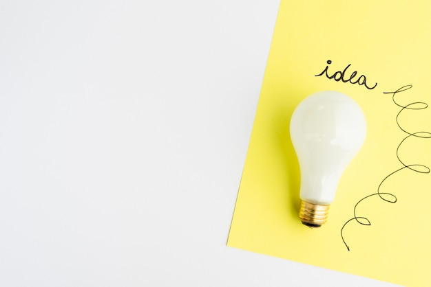 Idea text written on adhesive note with light bulb over white background