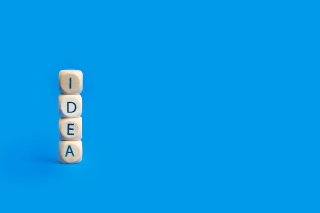 Слово идеи из деревянных блоков букв на синем фоне