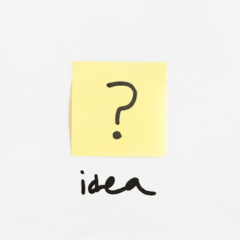 Idea word near adhesive note with question mark sign