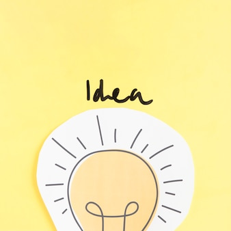 Idea word over paper cutout light bulb on yellow backdrop