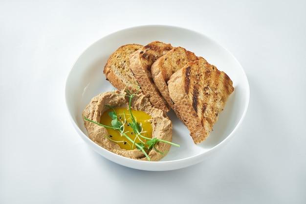理想的な前菜-白い背景の上の白いプレートにマンゴーソースとライ麦パンを添えた七面鳥の肝臓のパテ