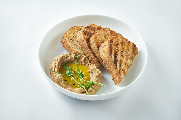Ideal appetizer - turkey liver pate with mango sauce and rye bread in a white plate on a white background
