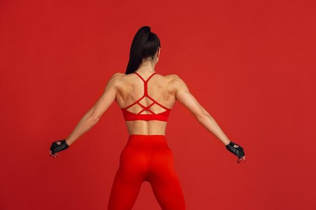 이상적인 몸. 스튜디오, 단색 빨간색 초상화 연습 아름 다운 젊은 여성 운동 선수.