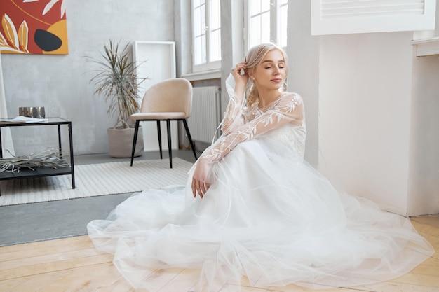 床に座っている理想的な花嫁、長い白いドレスを着た女の子の肖像画。美しい髪と清潔で柔らかい肌。結婚式の髪型金髪