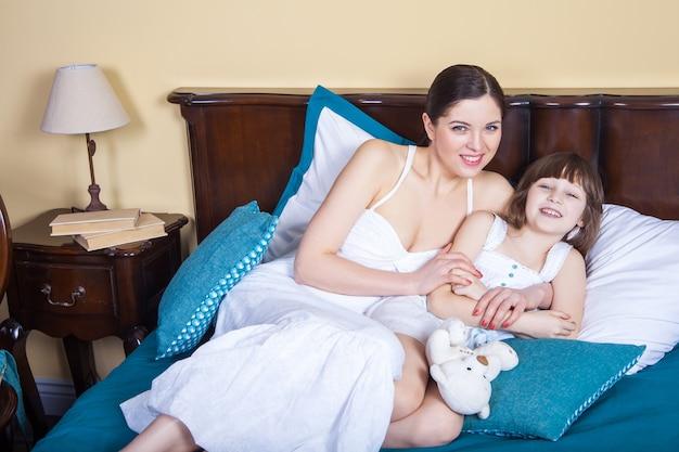 Идеальные отношения в семье. мама и дочь лежат в постели утром после пробуждения и смотрят в камеру с зубастой улыбкой. внутренний снимок