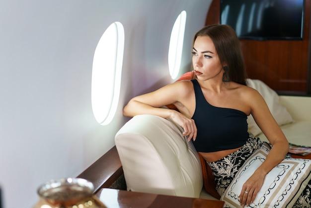Идеальная женщина современная женщина в стильной одежде улыбается, сидя у окна в первом классе ...