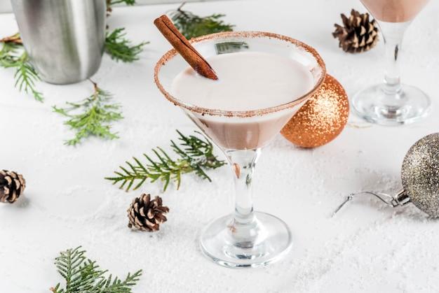 Идеи и рецепты новогоднего напитка eggnog martini с палочками корицы на белом мраморном столе с новогодним украшением