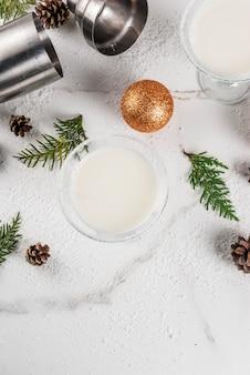 크리스마스 음료에 대한 아이디어와 요리법. 크리스마스 장식, 평면도와 흰색 대리석 테이블에 화이트 초콜릿 눈송이 마티니 칵테일