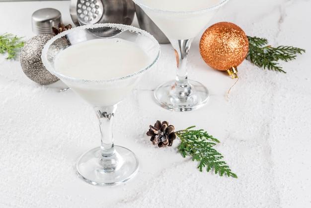 크리스마스 음료에 대한 아이디어와 요리법. 크리스마스 장식 흰색 대리석 테이블에 화이트 초콜릿 눈송이 마티니 칵테일