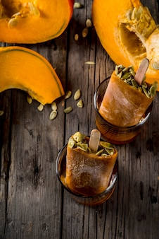 Ideas for autumn dishes from pumpkins. treats for a thanksgiving party, halloween. pumpkin ice cream popsicles with seeds, in glasses with maple syrup. on wooden old rustic table. copy space top view