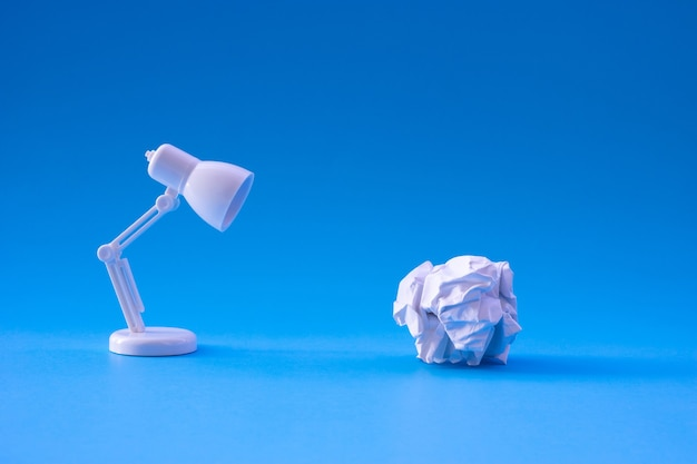 Ideas and creativity concepts with paper crumpled ball and lamp.