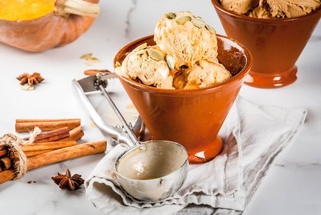 秋のデザートのアイデア、カボチャのレシピ。パンプキンパイアイスクリームジェラート、セラミックボウル、メープルシロップ、カボチャの種、シナモン、アニスの星、白い大理石のテーブルの上。コピースペース