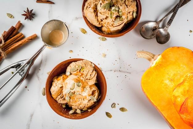 秋のデザートのアイデア、カボチャのレシピ。メープルシロップ、カボチャの種、シナモンとアニスの星、白い大理石のテーブルとセラミックボウルのパンプキンパイアイスクリームジェラート。コピースペースのトップビュー