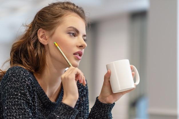 비즈니스를위한 아이디어. 집에서 공부하고 일합니다. 부엌에서 메모장을 사용 하여 메모를 만드는 사려 깊은 젊은 여자.