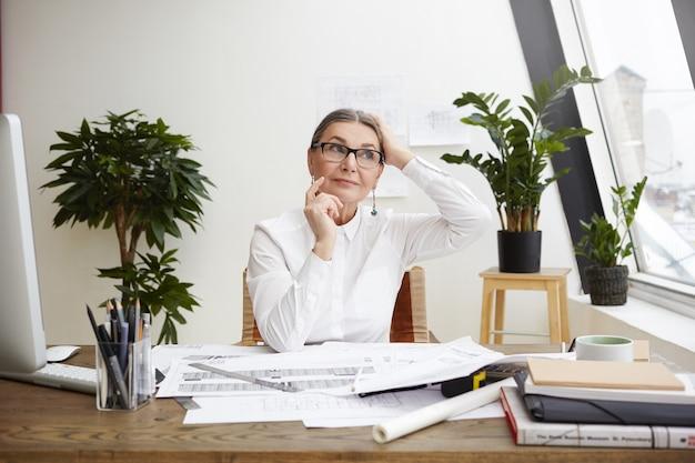 Idee, ispirazione e pensiero creativo. maschera dell'ingegnere maturo caucasico premuroso della donna in occhiali che osserva obliquamente con il sorriso misterioso e che indica il dito come se avesse grande idea