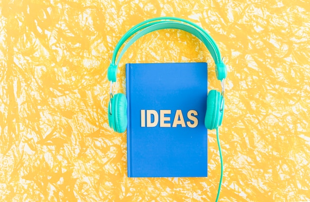 Ideas text on blue cover notebook with headphone on yellow backdrop