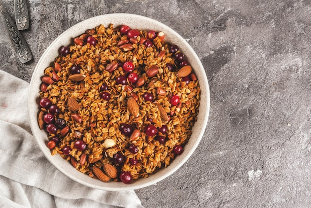 Ideas for a winter, autumn breakfast. thanksgiving, christmas. homemade fresh cooked honey granola with nuts (almonds, peanuts, hazelnuts) and cranberries. on gray concrete table, copyspace top view