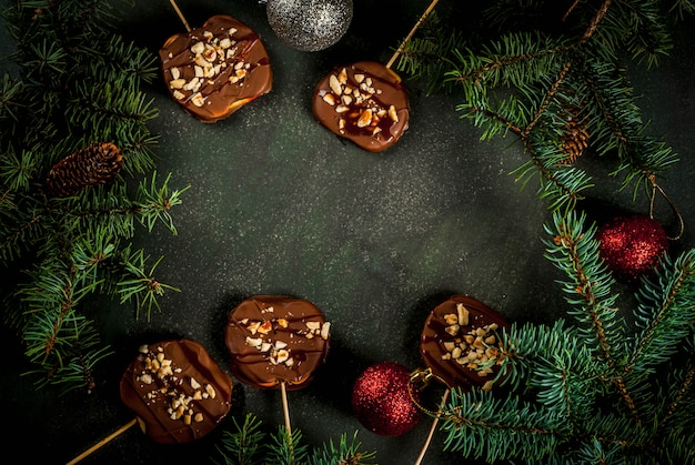 Ideas of winter, christmas treats. sweets for children. chocolate apple slices in chocolate, with caramel and nuts. dark green stone background, with christmas tree branches, top view frame copy space
