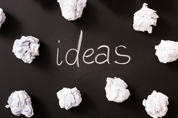 Ideas word surrounded with white crumpled paper balls on blackboard