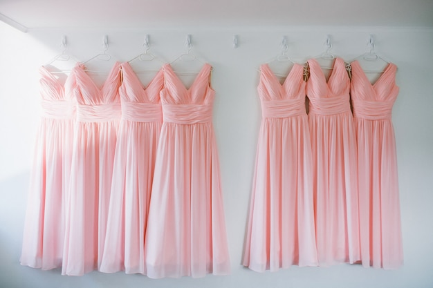 Идентичные подружки невесты розовые шифоновые платья на вешалках в ряд