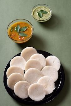 サンバーとココナッツのチャツネを添えたイドゥリ、インディアンディッシュ:南インドのお気に入りの食べ物、イドゥリまたはセモリナのイドゥリまたはラヴァのイドゥリ、サンバーとグリーンのチャツネを添えて。