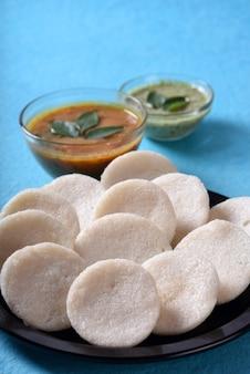 サンバーとココナッツチャトニーのイドゥリ、インディアンディッシュ:南インドのお気に入りの食べ物イドゥリまたはセモリナのイドゥリまたはラバのイドゥリ、サンバーとグリーンココナッツチャトニーを添えて。