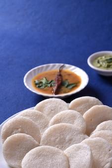 青い背景にサンバーとココナッツチャツネ、インド料理とイドゥリ