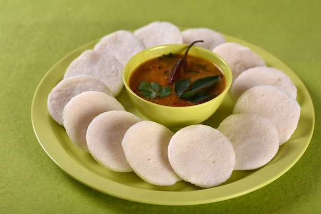 Idli with sambar in bowl on green background, indian dish