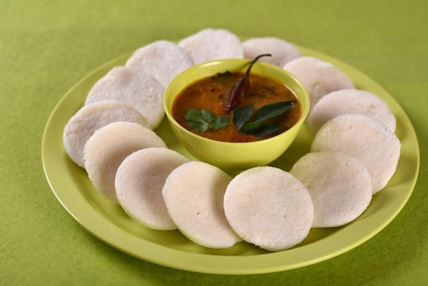 Idli with sambar in bowl, indian dish : south indian favourite food rava idli or semolina idly or rava idly, served with sambar and green coconut chutney.