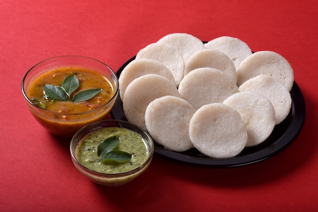 Idli with sambar and coconut chutney, indian dish : south indian favourite food rava idli or semolina idly or rava idly, served with sambar and green chutney.