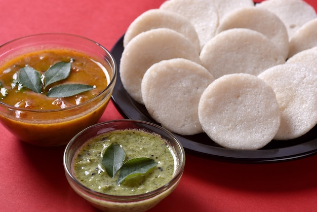 Idli with sambar and coconut chutney on red, indian dish