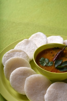 緑の表面にボウルにサンバーを入れたイドゥリ、インディアンディッシュ:南インドのお気に入りの食べ物ラヴァイドゥリまたはセモリナアイドリーまたはラヴァアイドリー、サンバーとグリーンココナッツチャトニーを添えて。