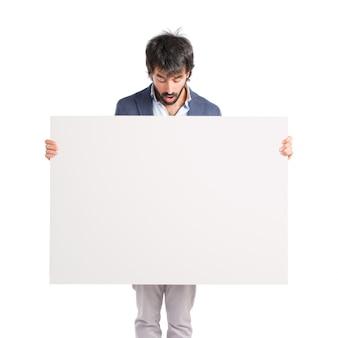 Idolatedの白い背景の上に空白のプラカードのビジネスマン