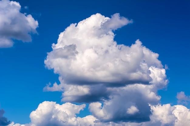 솜털과 뇌우 구름과 목가적 인 푸른 하늘