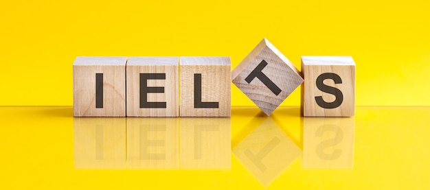 Ielts 단어는 노란색 테이블에 누워 있는 나무 빌딩 블록으로 만들어집니다.