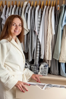 Ifcaucasian young woman housewe in a white terry robe holding container with underwear, socks and underpants. clothes storage.
