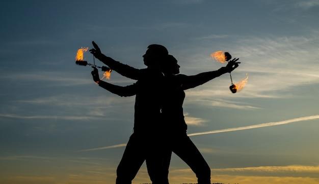 Зажги свое танцевальное пламя. танцующая пара вращает горящие пои. танцоры пламени на идиллическом небе. вечерние оттенки и светильники. пожарное исполнение. открытый фестиваль. ночная вечеринка. веселье и развлечение.