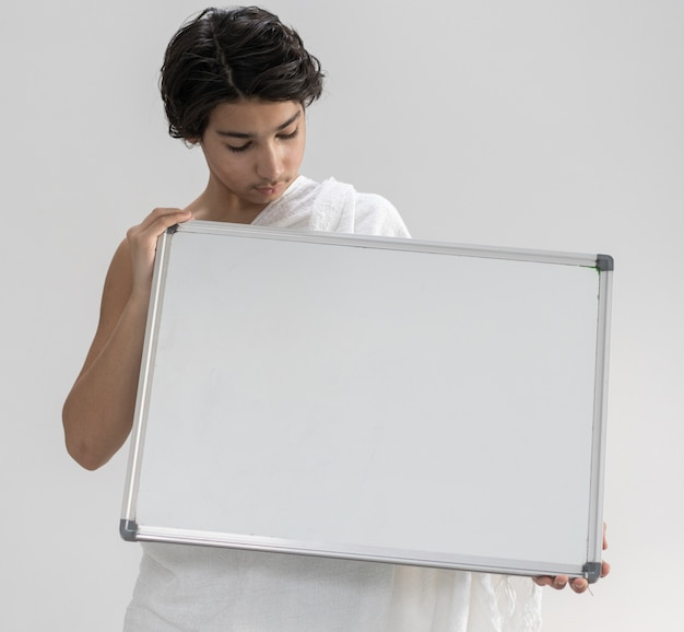 コピースペースボードを保持しているハッジのためのihramを着ている10代の少年