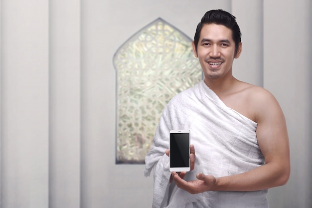携帯電話を保持しているihram服を着ているハンサムなアジアのイスラム教徒の男性