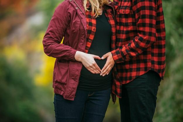 腹iin心に手を繋いでいる妊娠中のカップル