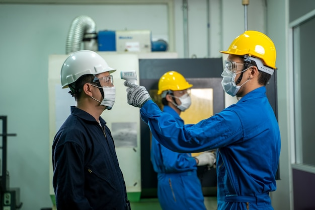 Iindustrial worker wear protective face mask scan temperature before working at factory