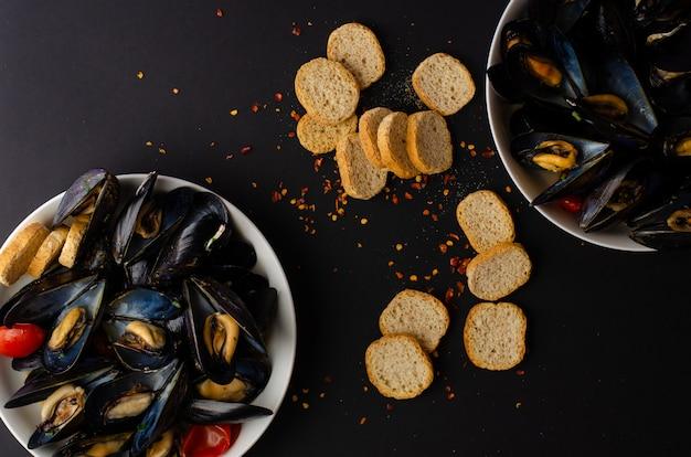 ムール貝のスープは黒の背景にトマト、唐辛子、ぱりっとしたパンとワインで蒸しました。 iitalianシーフード。フラット横たわっていた、トップビュー、コピースペース