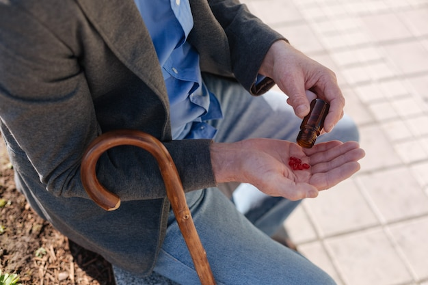 Ill aged disappointed pensioner carrying about his health taking pills while having a break